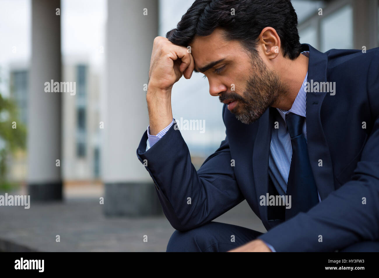 Depressed businessman sitting with hand on forehead in the office premises - Stock Image