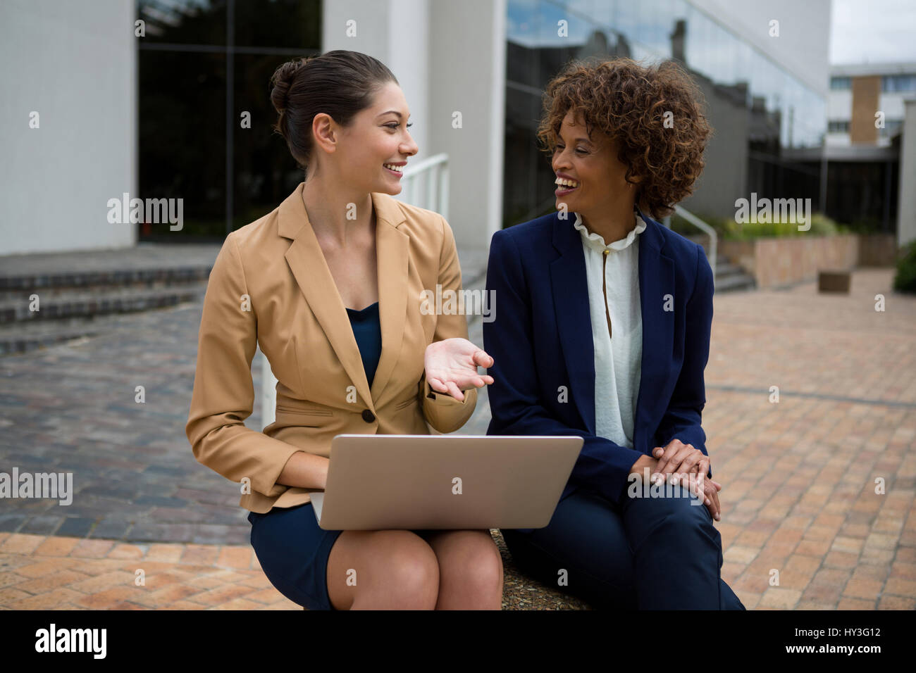 Portrait of two businesswomen interacting with each other in the office premises - Stock Image