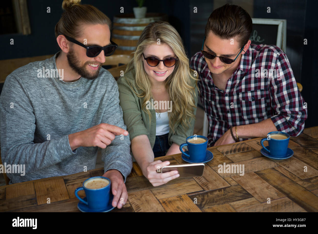 Smiling young friends using smart phone at table in cafe - Stock Image