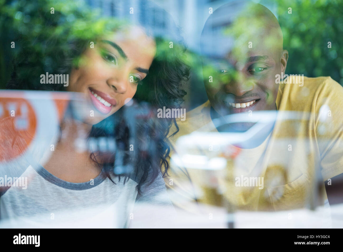 Smiling young couple in coffee shop seen through window - Stock Image