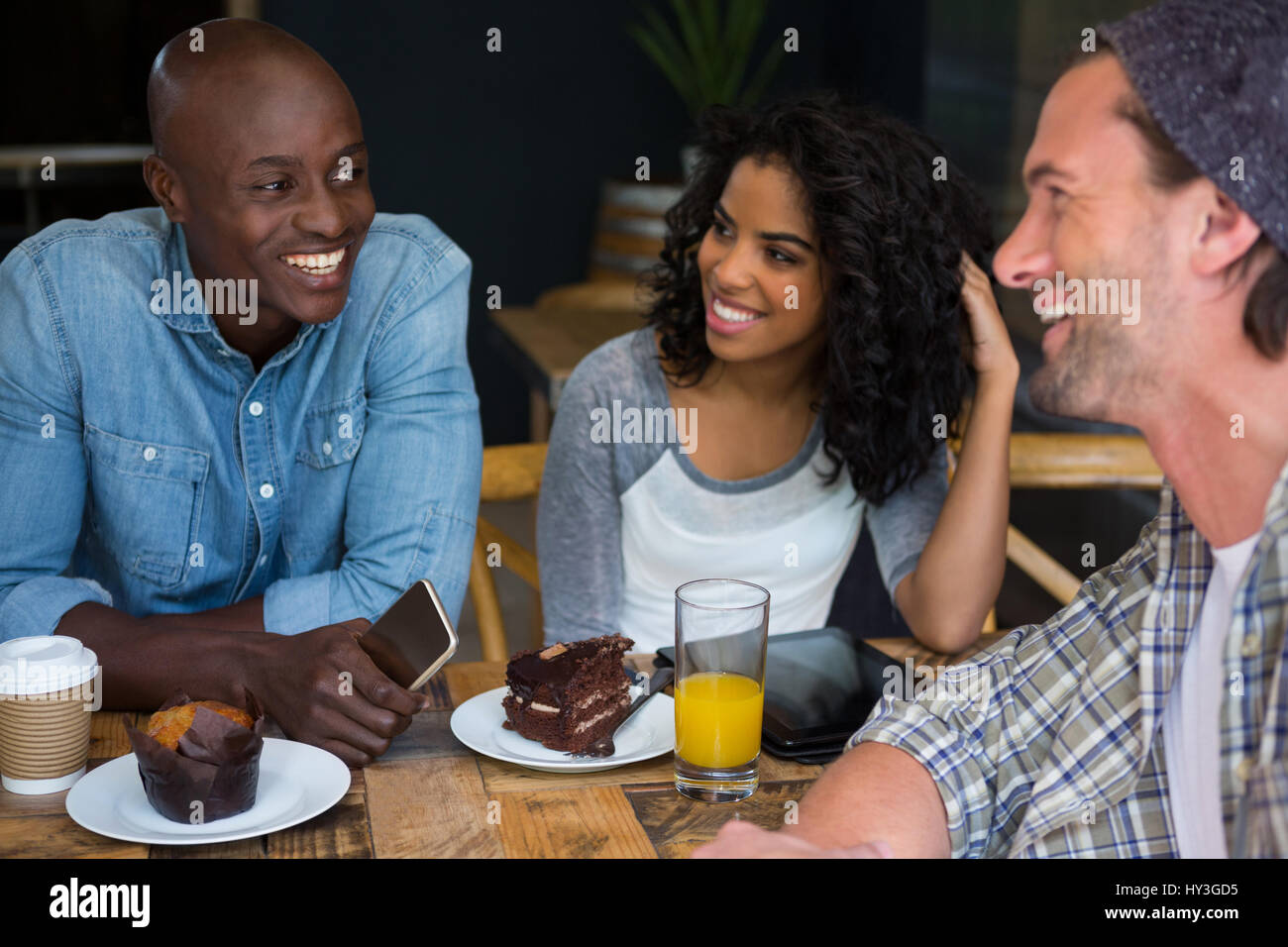Male and female friends talking at table in coffee house Stock Photo