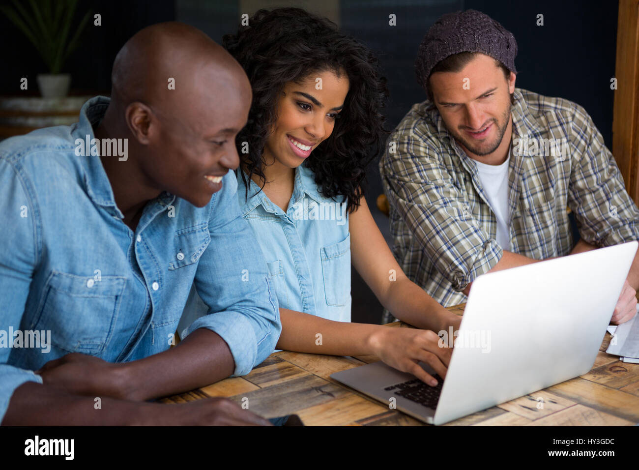 Happy friends using laptop at wooden table in coffee shop - Stock Image