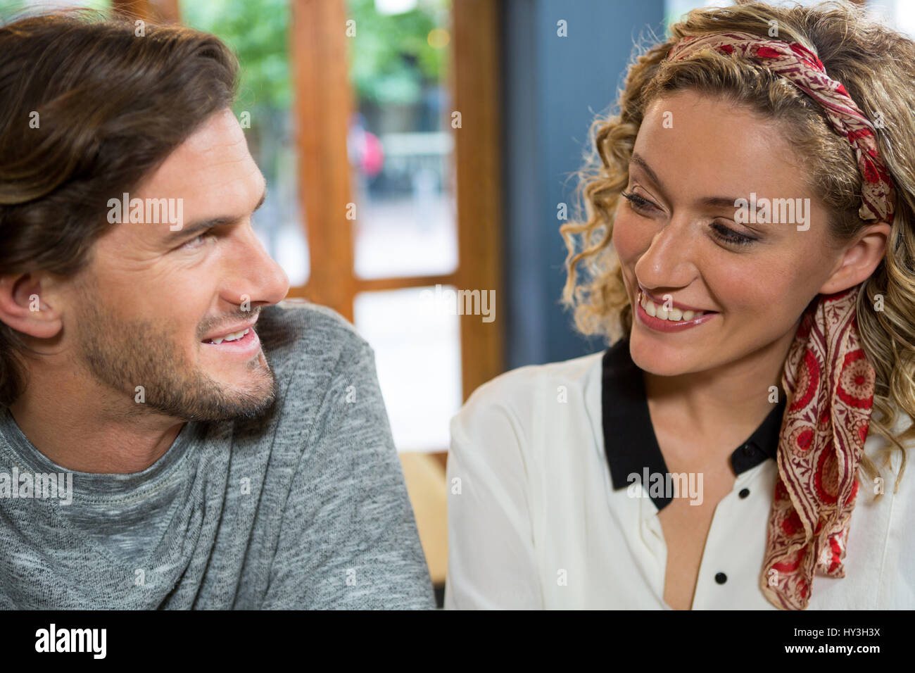 Smiling young couple looking at each other in coffee shop - Stock Image
