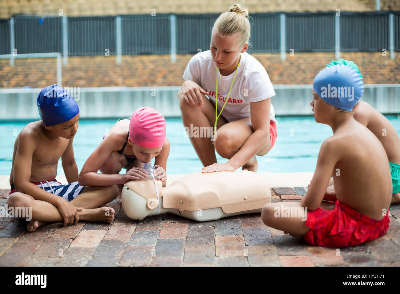 c0588ec951c Female lifeguard helping children during rescue training at poolside -  Stock Image