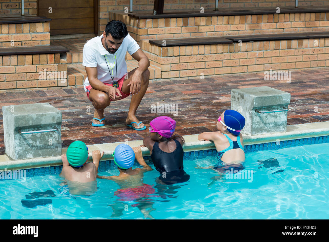 Male instructor advising little swimmers at poolside - Stock Image