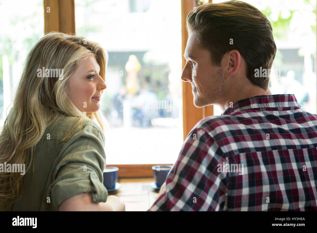 Loving young couple looking at each other in coffee house - Stock Image