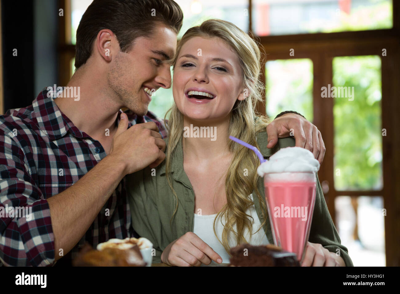 Romantic young couple spending quality time in coffee shop - Stock Image