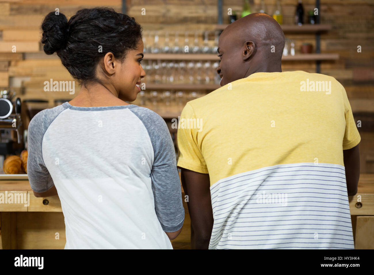 Rear view of young couple looking at each other in coffee shop - Stock Image