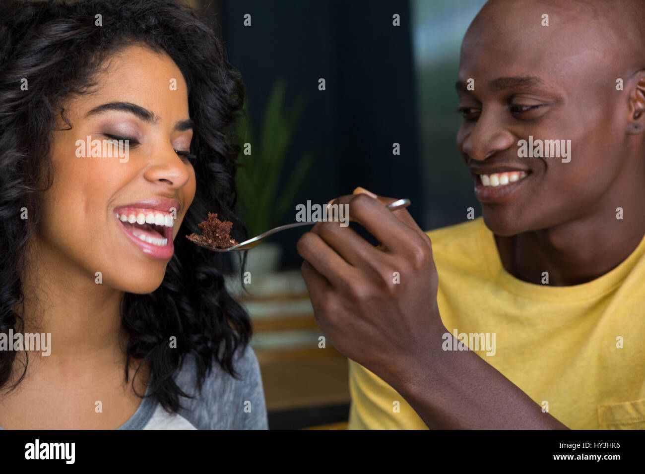 Loving young man feeding dessert to woman in coffee shop - Stock Image
