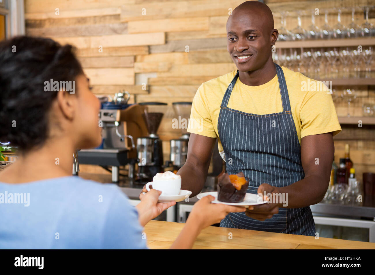 Portrait of male barista serving coffee and dessert to female customer in cafe - Stock Image