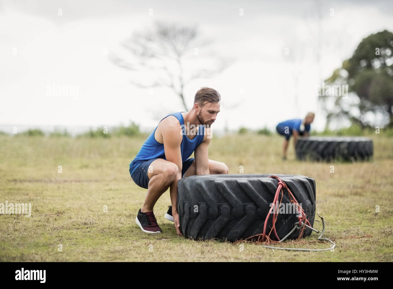 Fit woman flipping a tire during obstacle course in boot camp - Stock Image