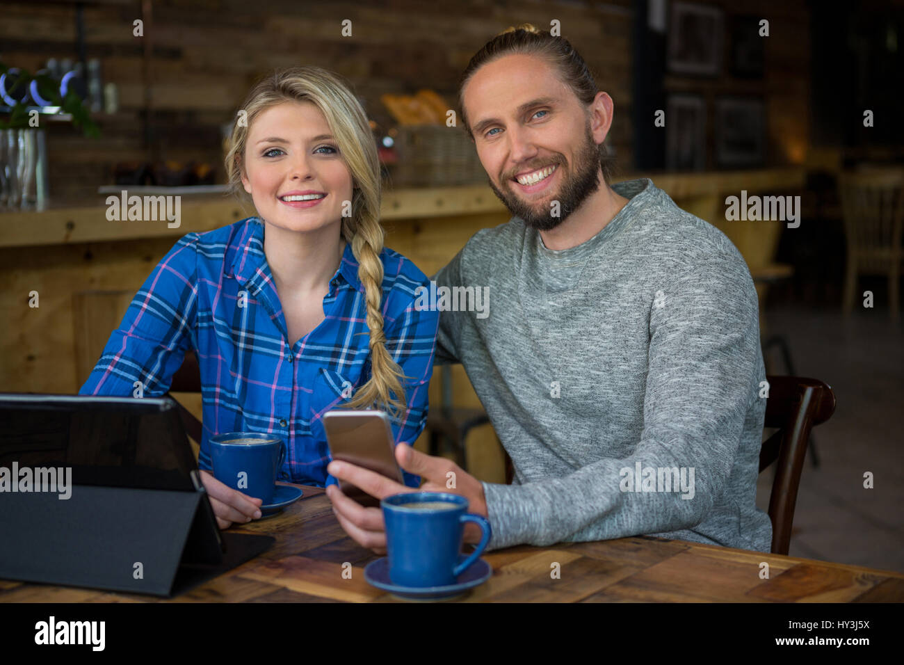 Portrait of smiling young couple with coffee and technologies in cafe - Stock Image