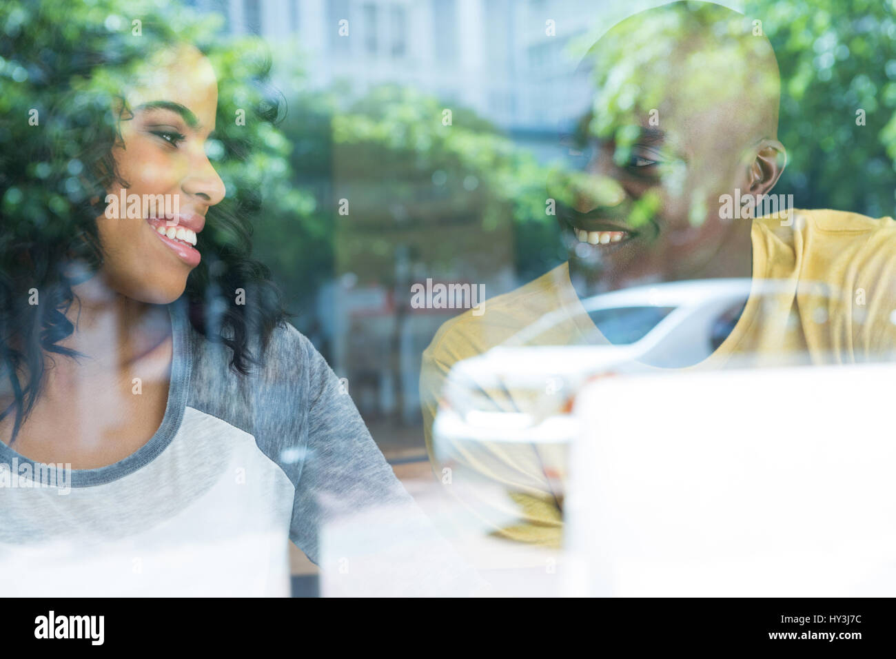 Loving young couple looking at each other in coffee house seen through window - Stock Image