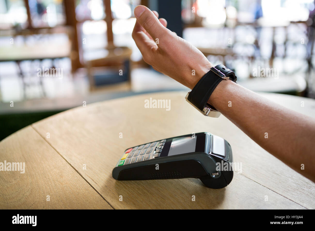 Cropped image of man hand using smart watch to express pay in coffee shop - Stock Image