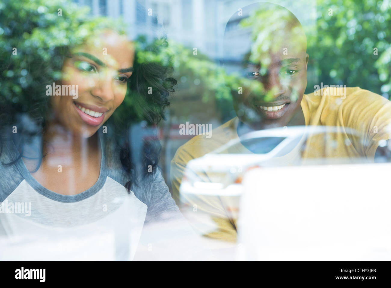 Smiling multi ethnic young couple in coffee shop seen through window - Stock Image