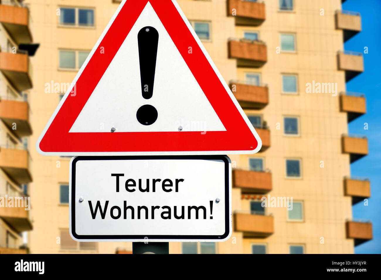 Road sign with label expensive living space before a high rise, symbolic photo rent price brake, Verkehrsschild Stock Photo