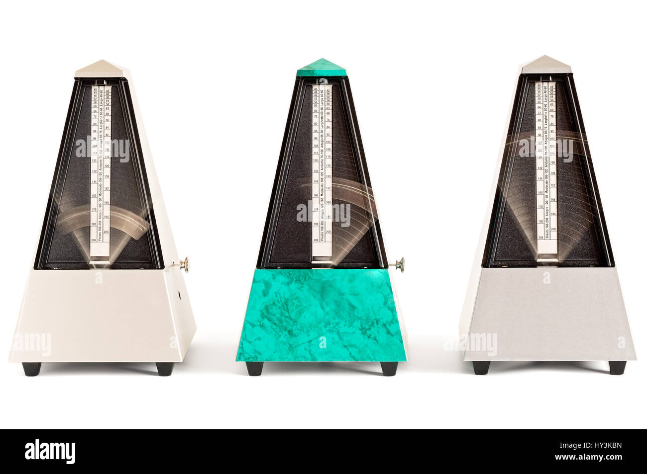 Three swinging pyramid shaped metronomes in plastic housing isolated on white - Stock Image