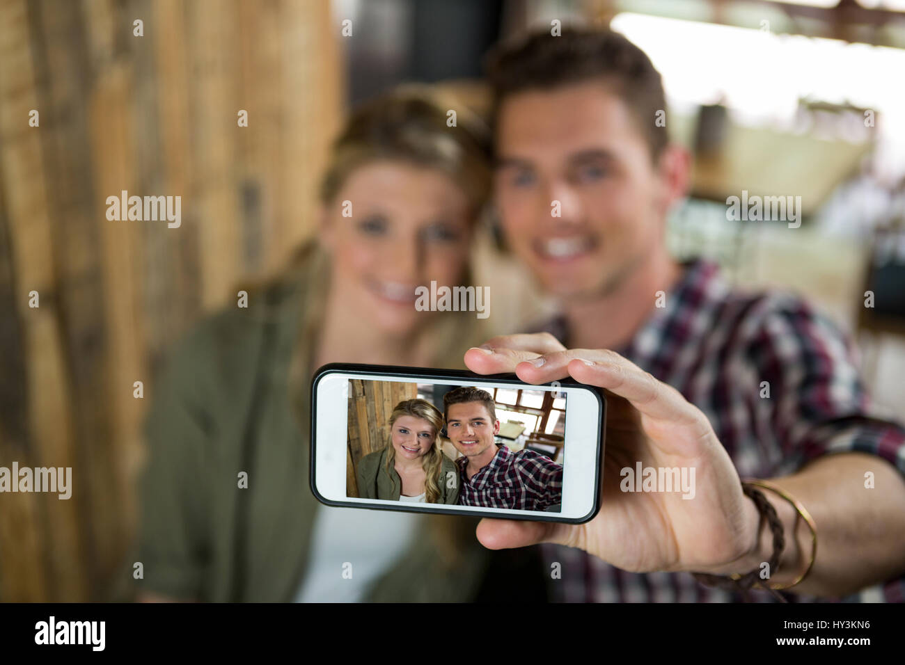 Smiling young couple taking selfie with cellphone in cafeteria Stock Photo