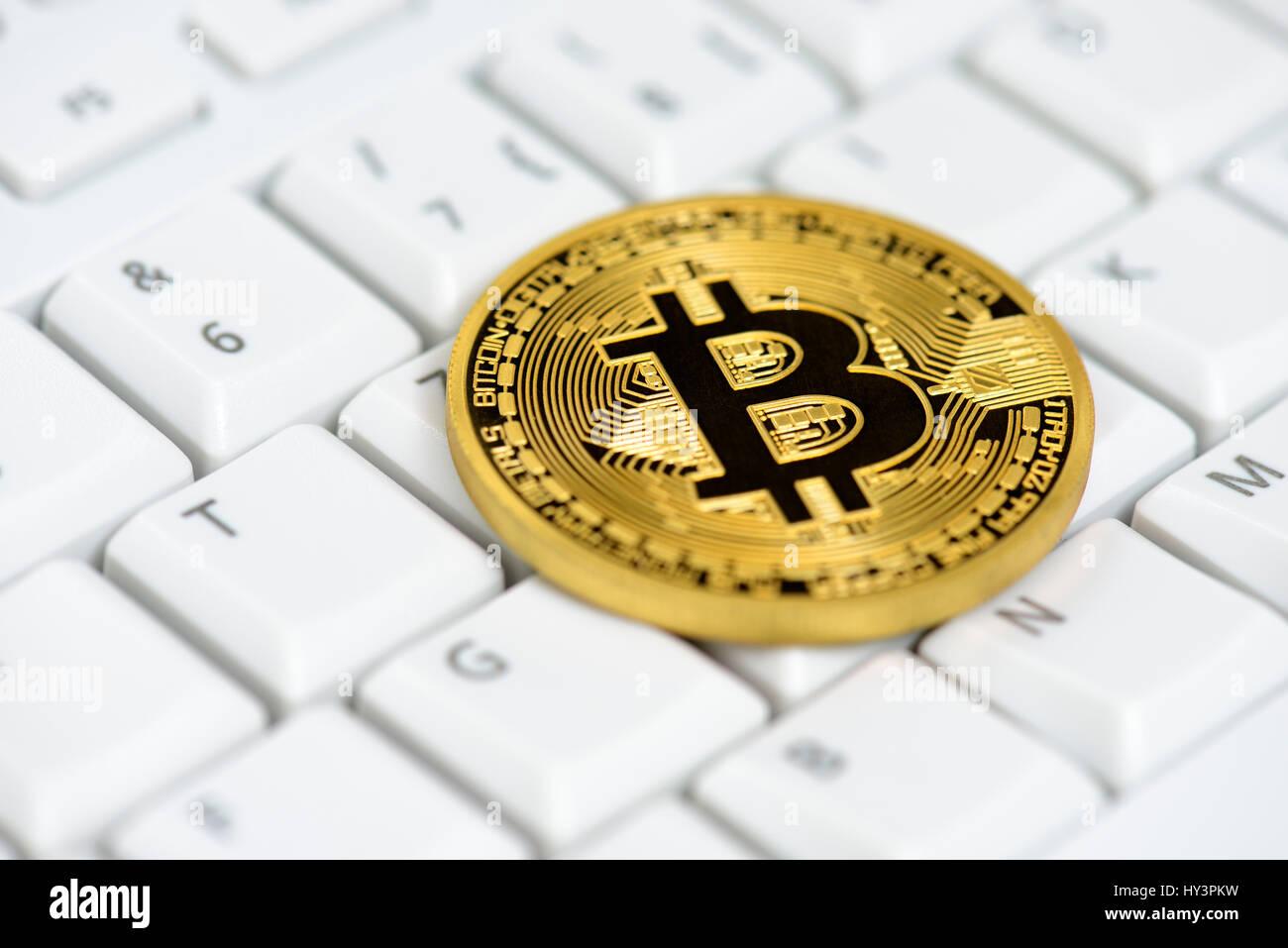 Coin with Bitcoin sign on computer keyboard, Münze mit Bitcoin-Zeichen auf Computertastatur Stock Photo