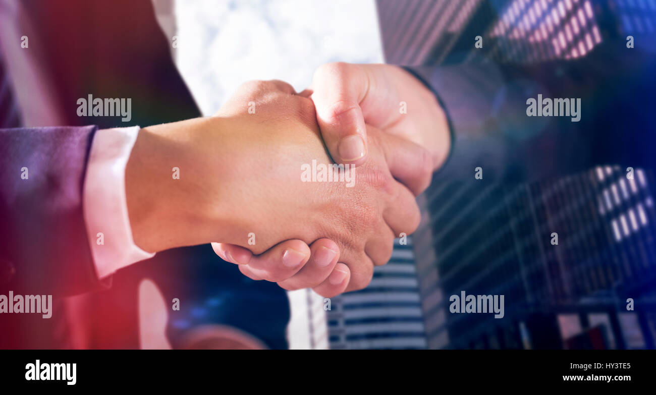Male and female corporates shaking hands against view of modern office building - Stock Image