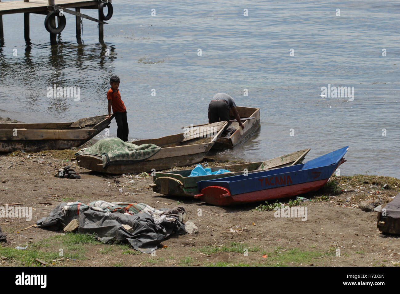 Young kid is watching his father preparing a boat for fishing on Atitlan Lake in Guatemala - Stock Image