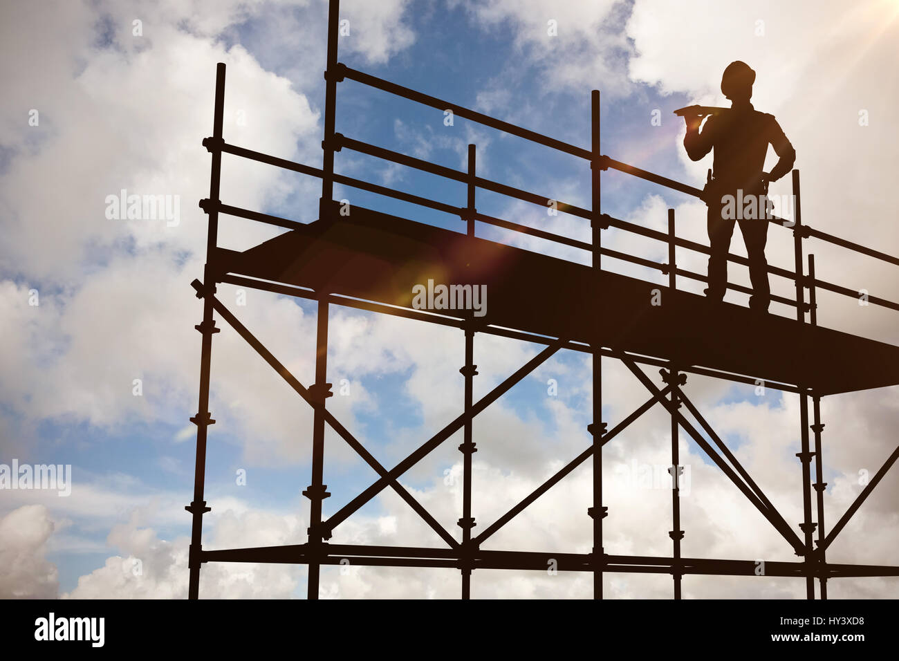 Thoughtful worker carrying wooden planks against blue sky with white clouds - Stock Image