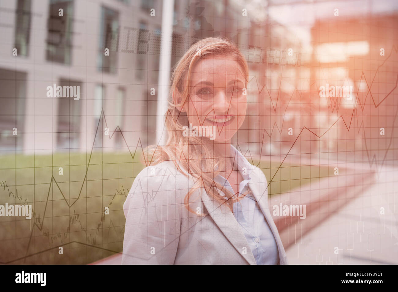 Stocks and shares against smiling businesswoman standing in office premises - Stock Image
