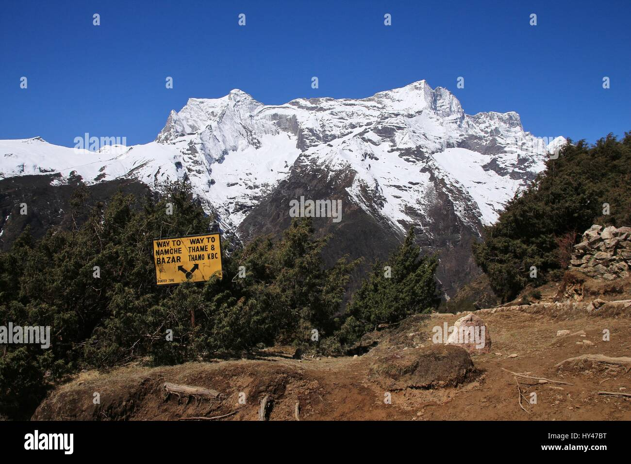 Directional sign and snow capped mountain. Scene near Namche Bazar, Everest National Park. - Stock Image