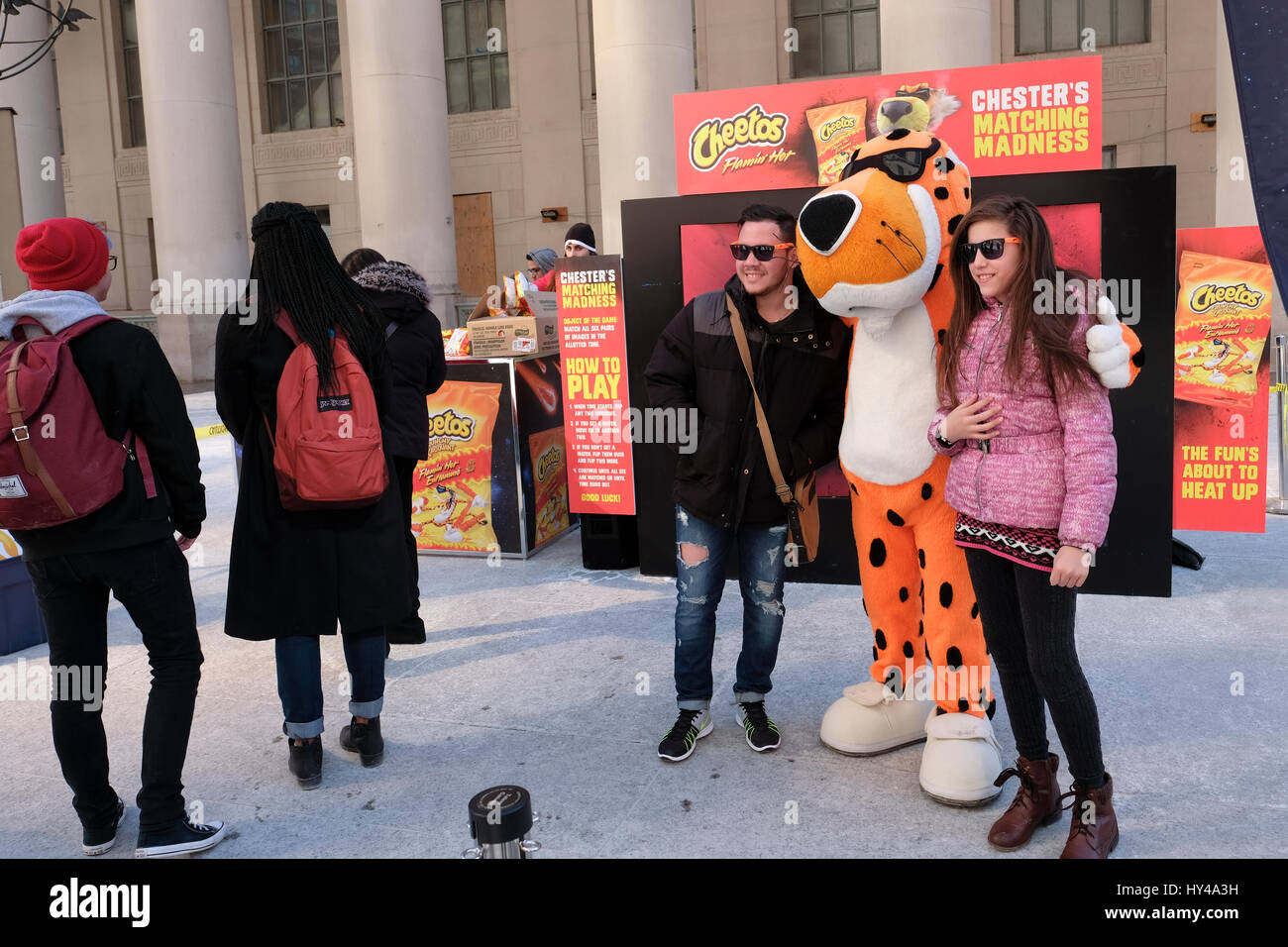 Cheetos Chester Cheetah and promotional crew distributing free samples of Cheetos Flamin Hot cheese snacks to consumers - Stock Image