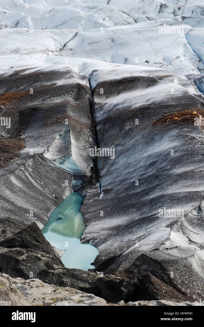 Above view on Iceland's glacier melting and turning into a dirty black crevasse of ice with a turquoise lake - Stock Image