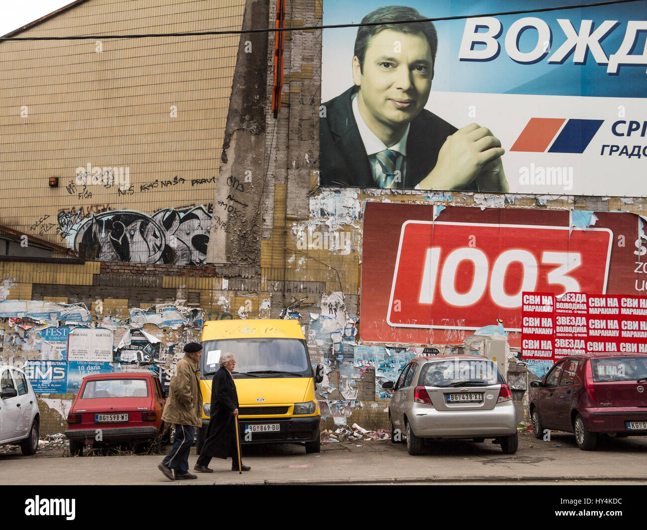BELGRADE, SERBIA - MARCH 8, 2015: Old people walking in front of a propaganda poster for the Prime Minister Aleksandar - Stock Image