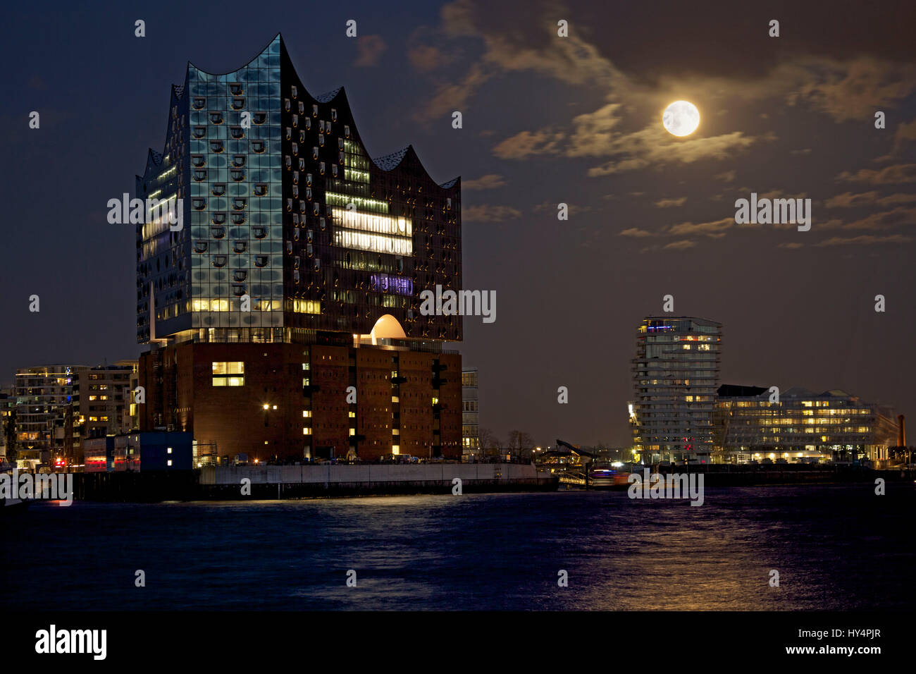 The full moon is  in the sky behind the Elbphilharmonie / Elbe Philharmonic Hall, right side of Vasco Da Gama Tower - Stock Image