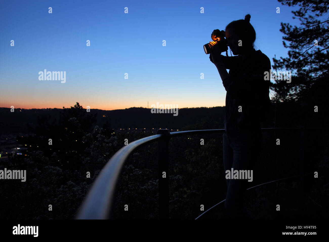Young woman photographed down to the city with flash - Stock Image