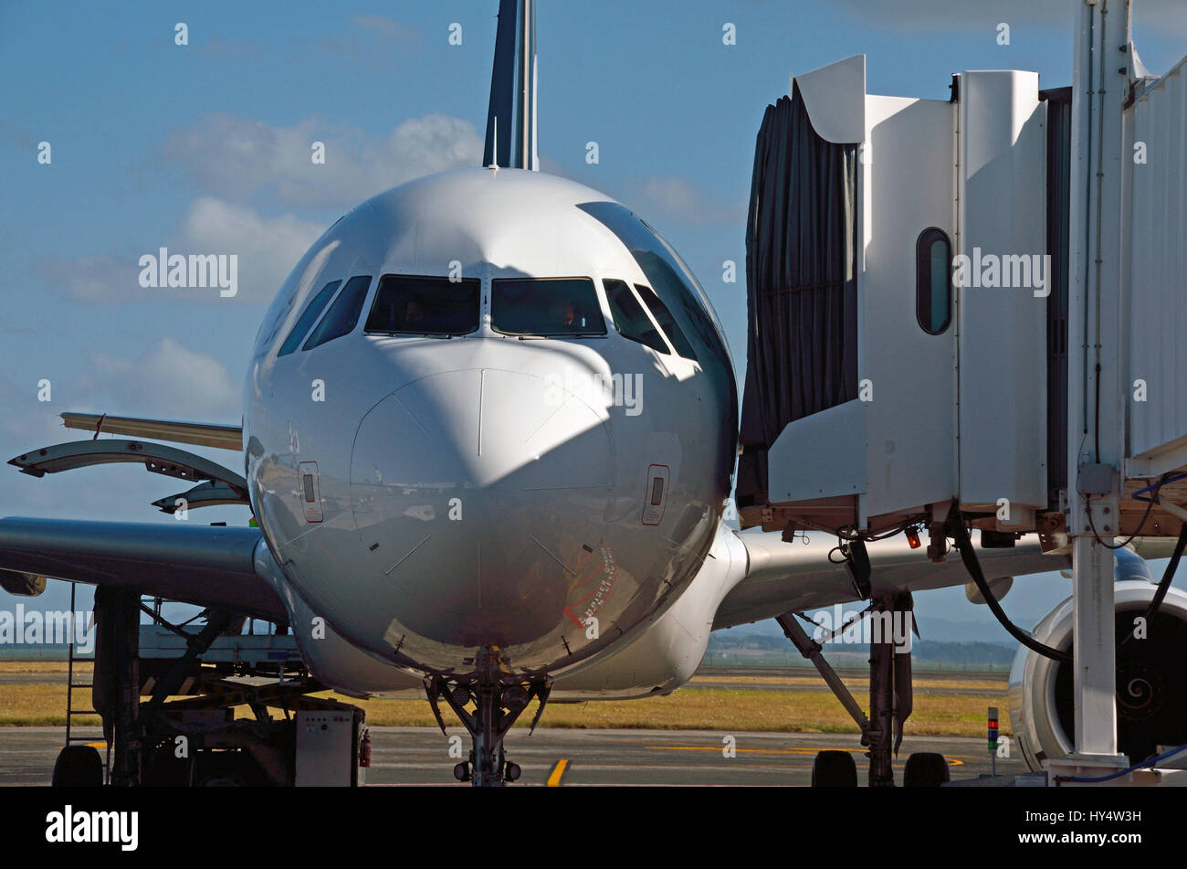 the walkway closes in on a passenger jet as passengers wait to embark. - Stock Image
