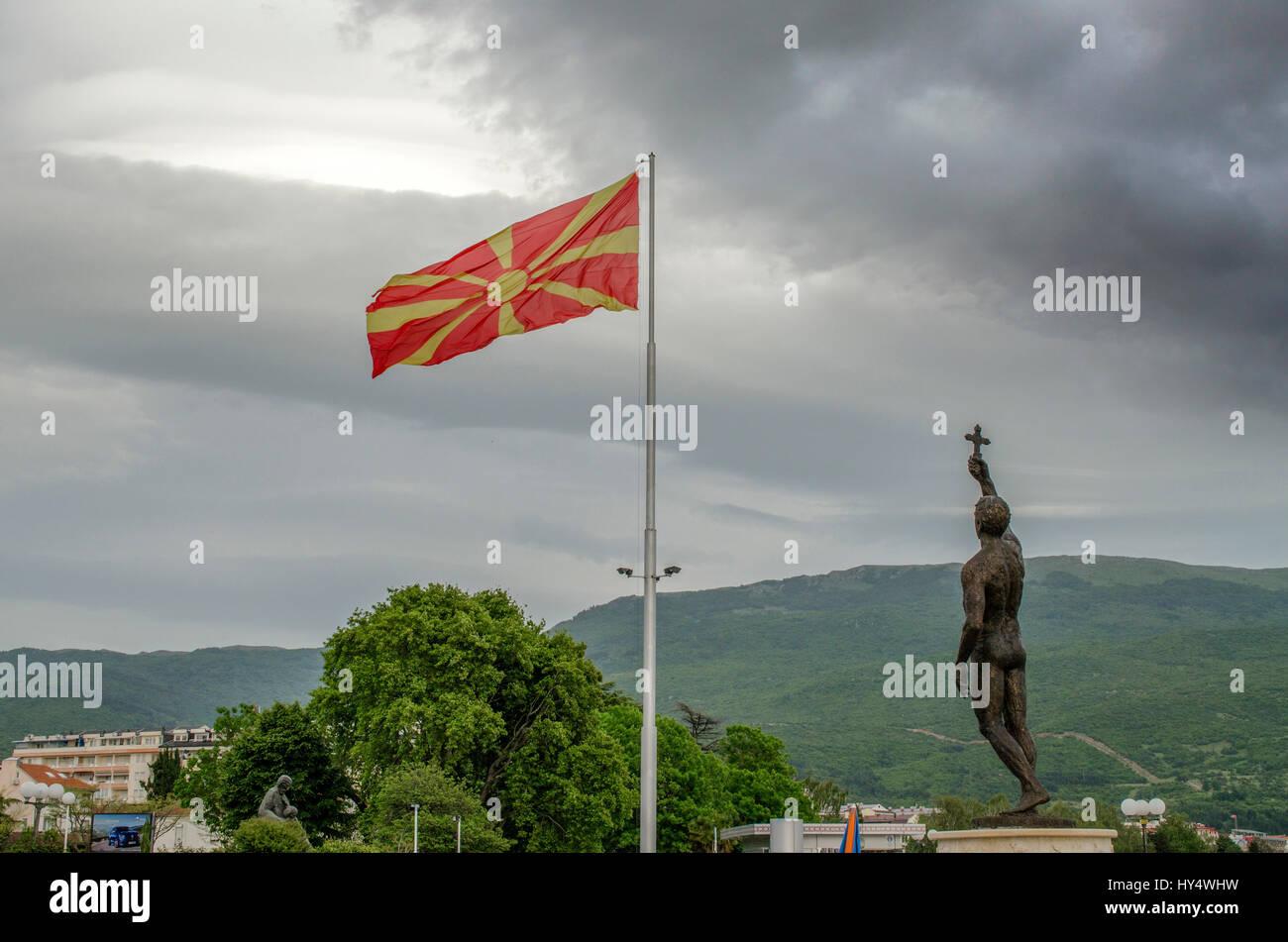 Macedonian flag with monument 'Epiphany' in Ohrid, Macedonia - Stock Image