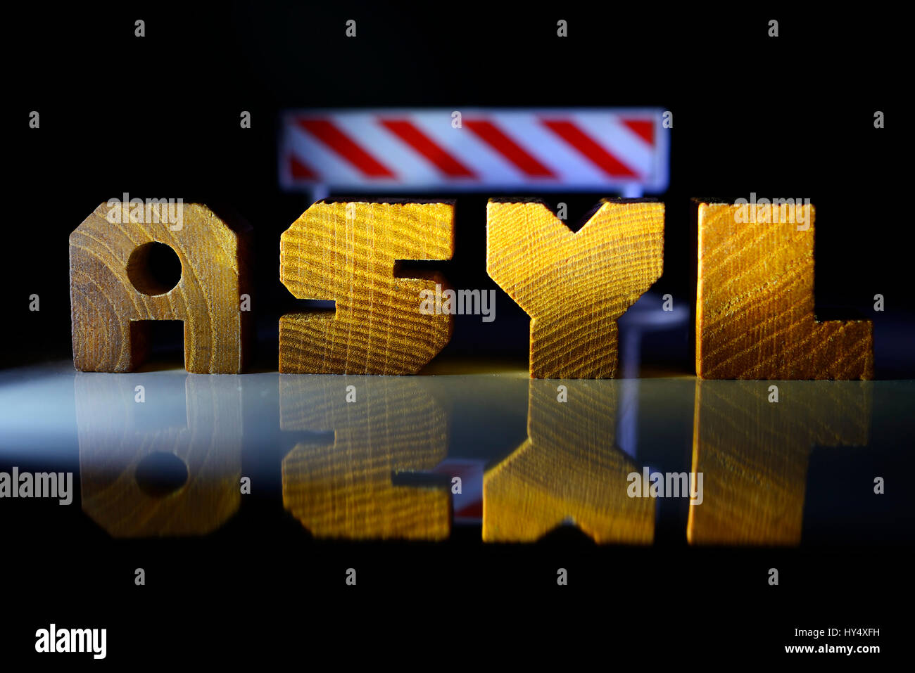 The word Asylum from wooden letter and locking beam, upper limit for refugees, Das Wort Asyl aus Holzbuchstaben - Stock Image