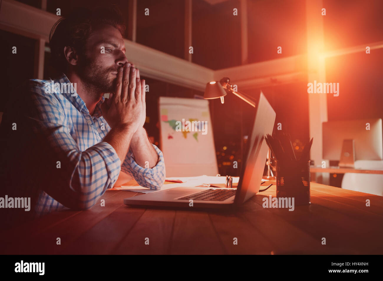 Overworked businessman working at night in office - Stock Image
