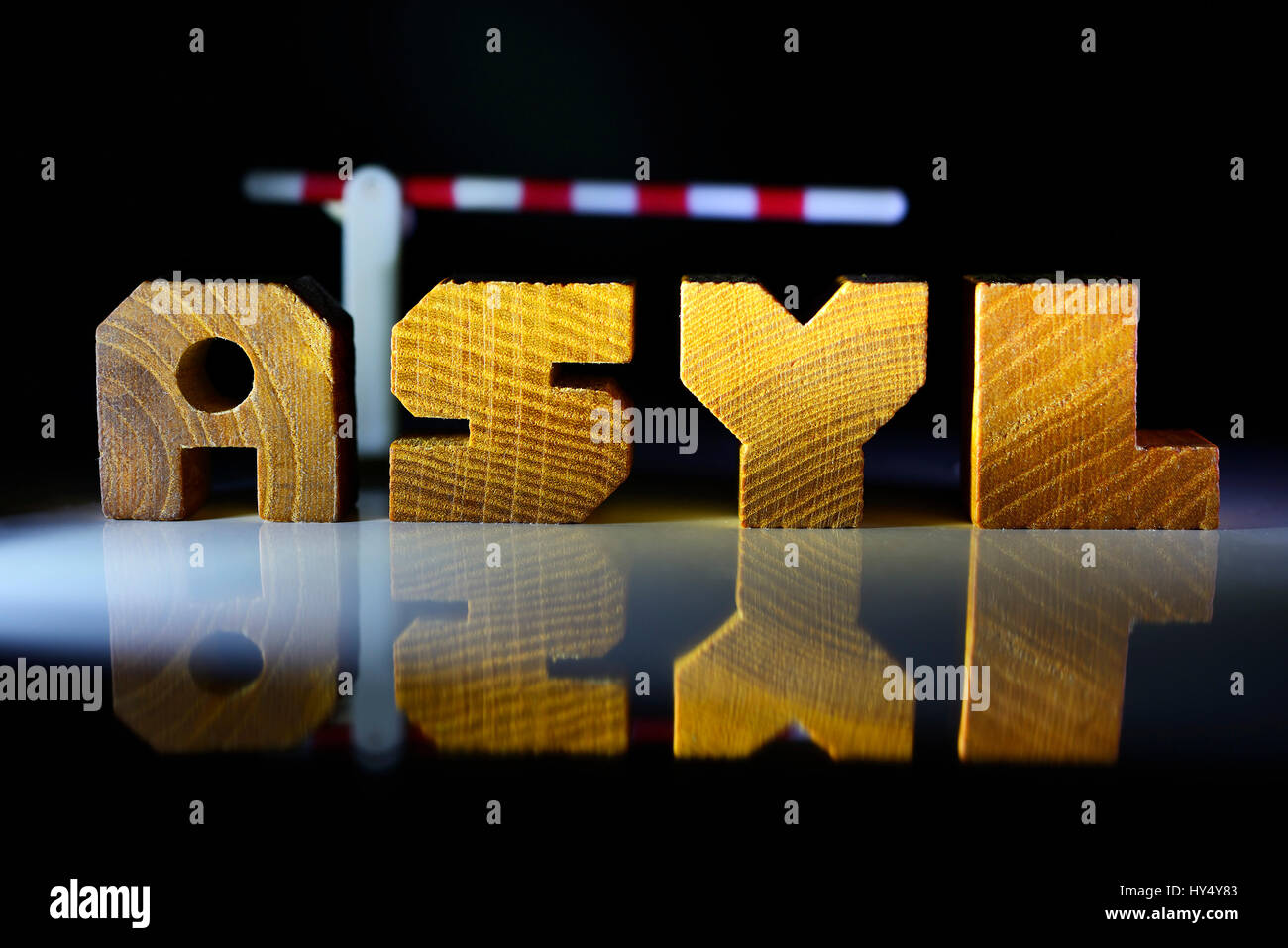 The word Asylum from wooden letter and tollgate, upper limit for refugees, Das Wort Asyl aus Holzbuchstaben und - Stock Image