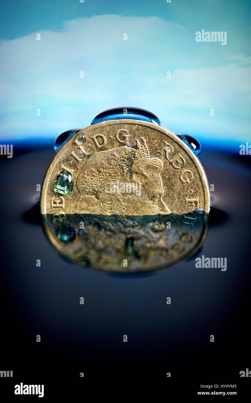 British one-pound coin in the water, low pound course, Britische Ein-Pfund-Muenze im Wasser, niedriger Pfund-Kurs Stock Photo