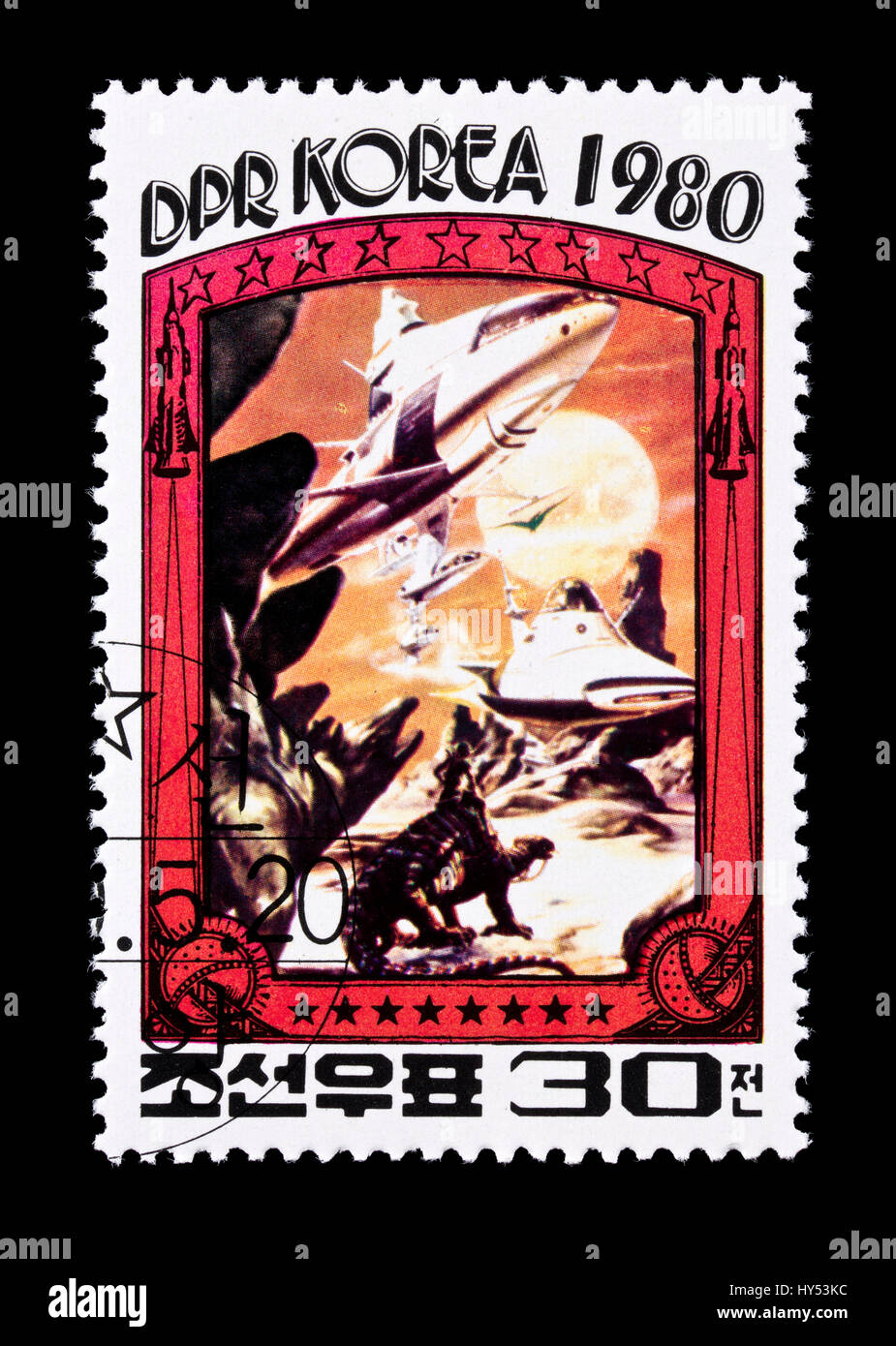 Postage stamp from North Korea depicting a spaceship landing on another planet being greeted by dinosaurs - Stock Image