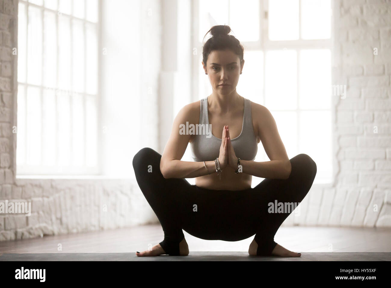 Young attractive woman in Malasana pose, white loft studio backg - Stock Image