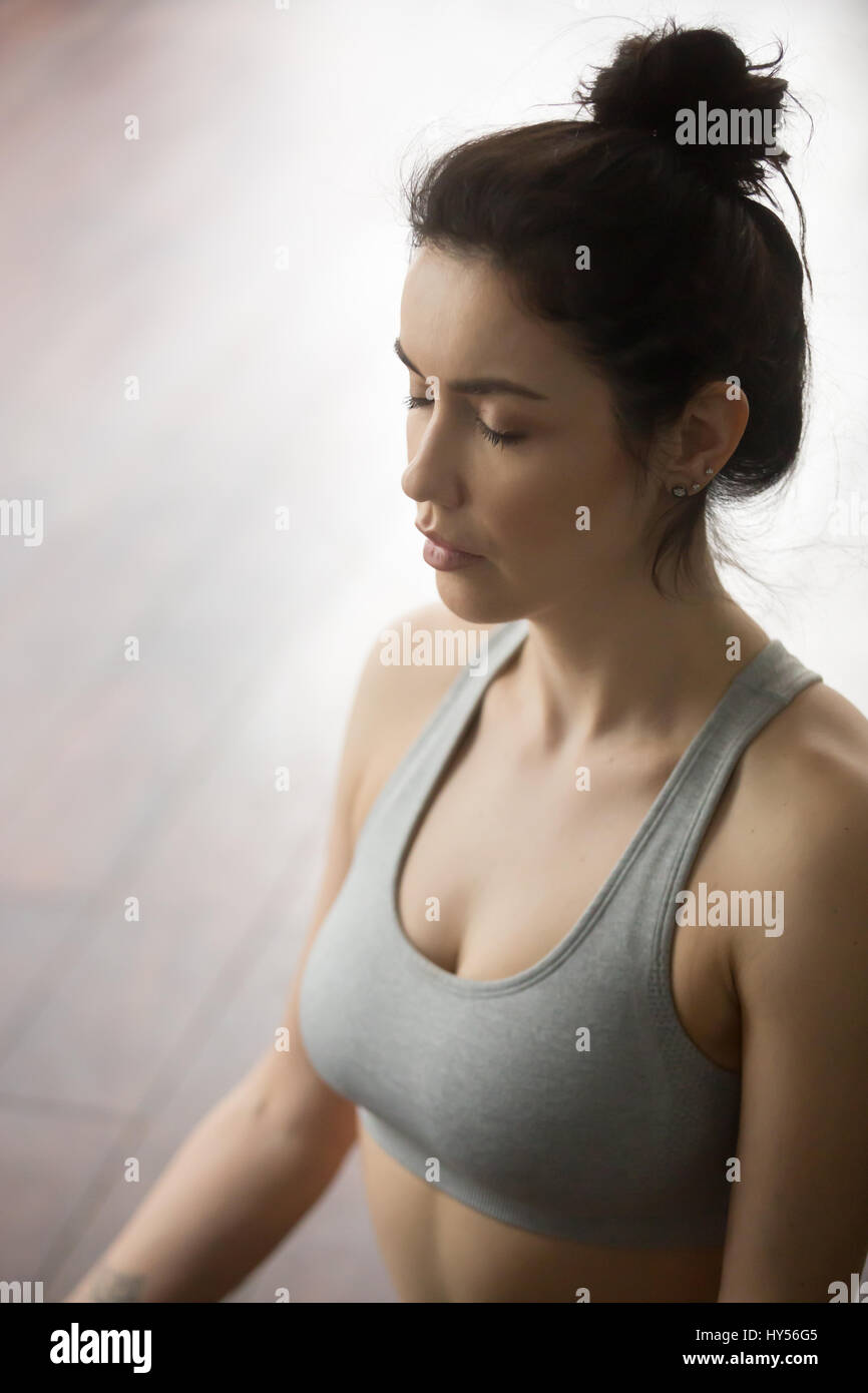 Portrait of young attractive woman meditating in yoga pose, stud - Stock Image