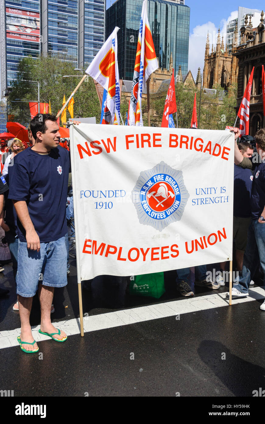 Off-duty firefighters hold the banner of their trade union banner during a protest. Trade unionism; union activism; - Stock Image