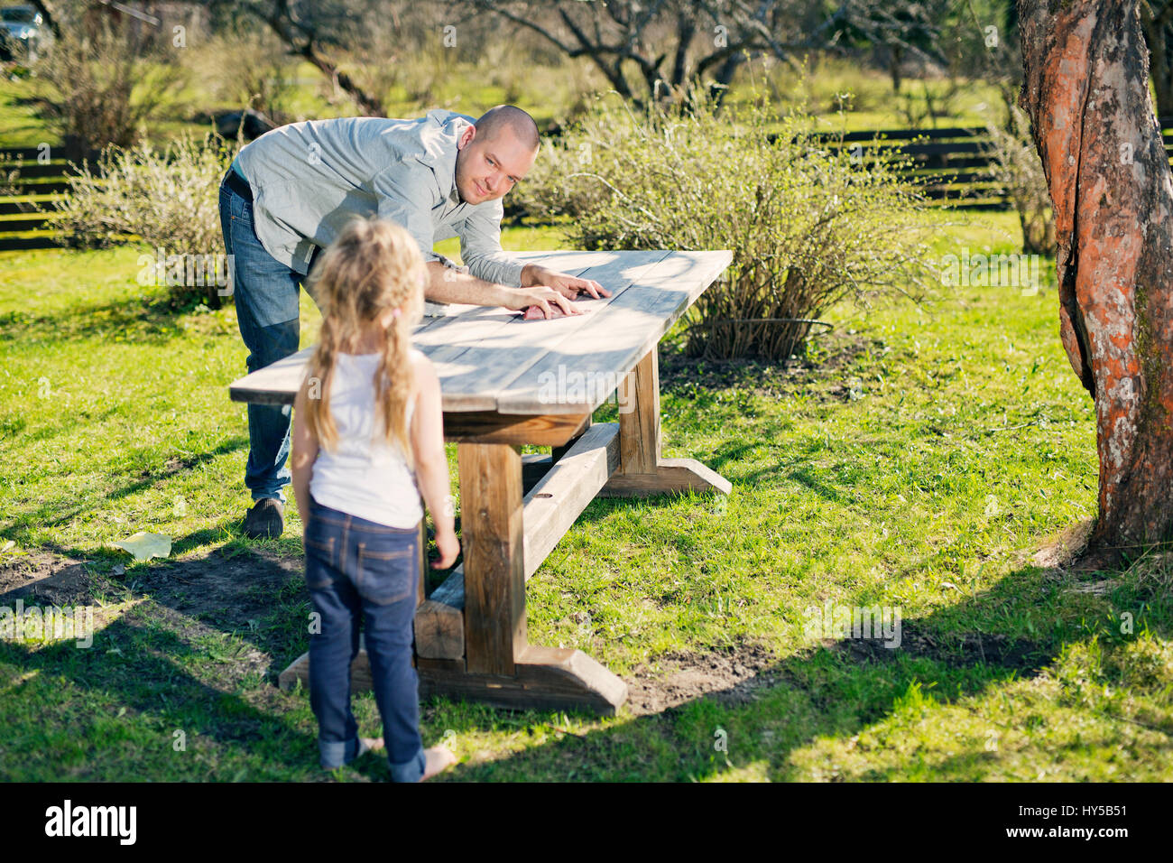 Finland, Paijat-Hame, Heinola, Father with daughter (4-5) polishing wooden table in garden - Stock Image