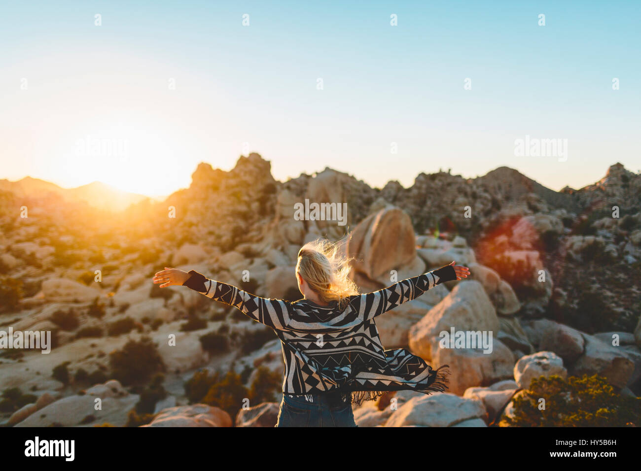USA, California, Woman spreading arms in Joshua Tree National Park - Stock Image