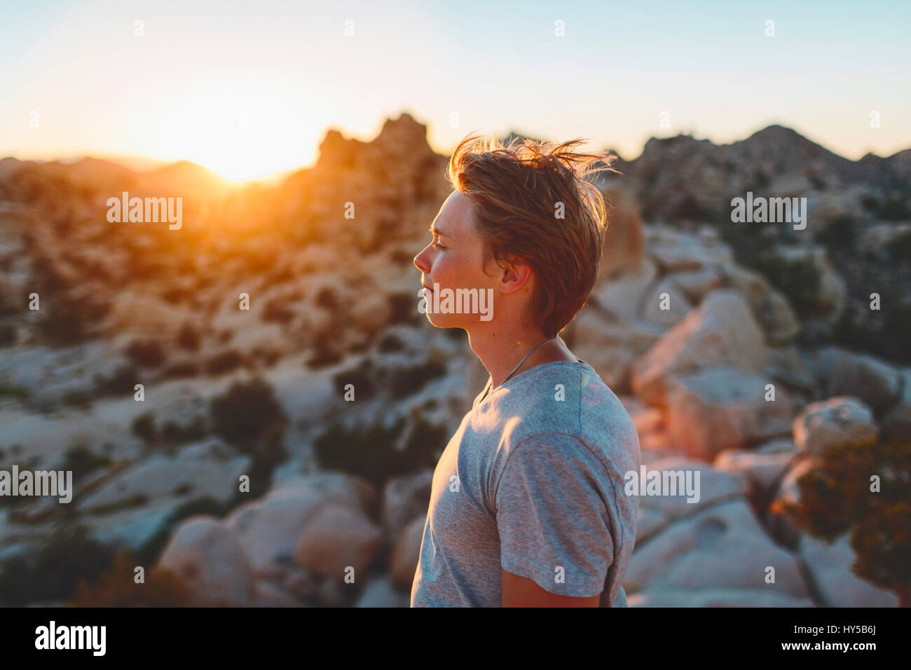 USA, California, Joshua Tree National Park, Young man contemplating at sunset - Stock Image