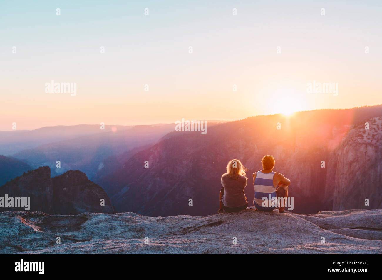 USA, California, Yosemite National Park, Taft Point, Man and woman watching sunset in mountains - Stock Image