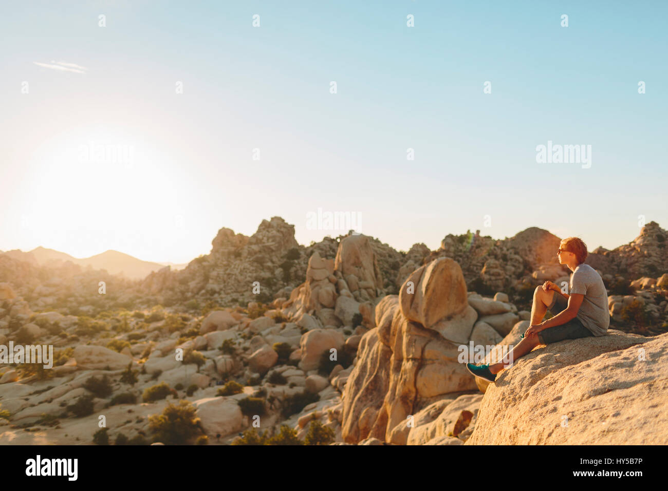 USA, California, Joshua Tree National Park, Man sitting on rock and looking at rocks - Stock Image