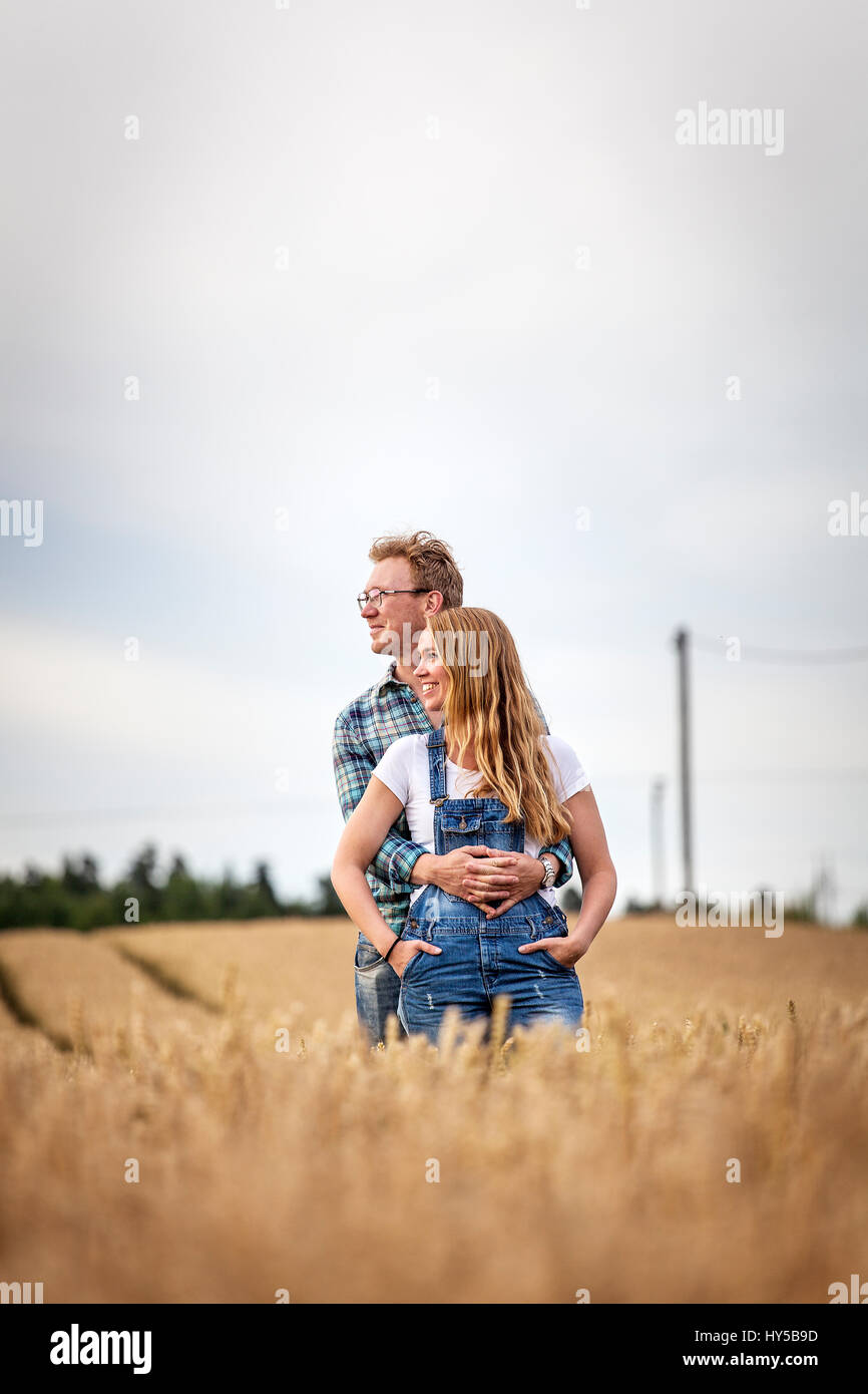 Finland, Uusimaa, Siuntio, Mid adult couple embracing in wheat field - Stock Image