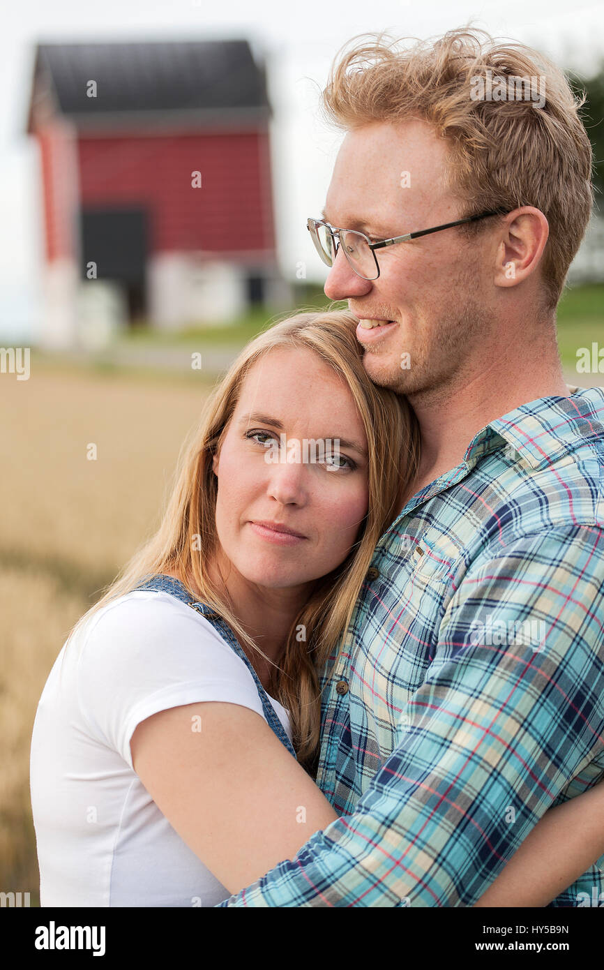 Finland, Uusimaa, Siuntio, Mid adult couple embracing in field - Stock Image